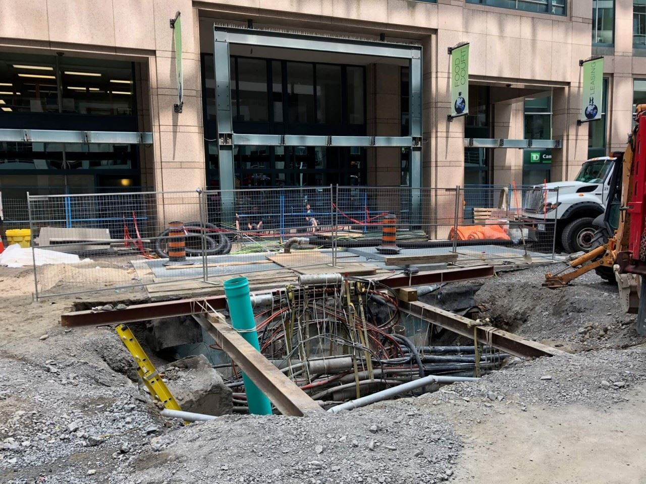 Open work hole on Queen Street, showing exposed wires, conduits and connections.
